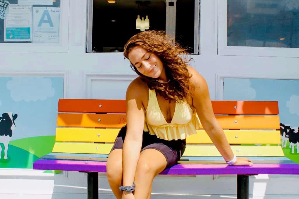 Jenna Haith on a rainbow bench in california, venice beach